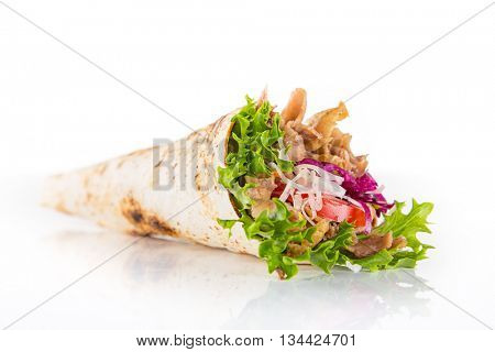 Kebab sandwich in tortilla on wooden background