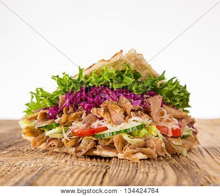 Kebab in pita on old wooden table.