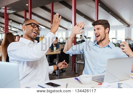 Two cheerful excited young men giving high five and working in office together