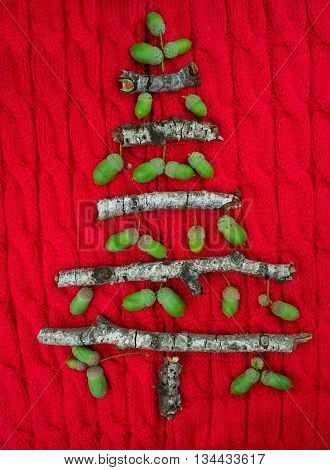 Christmas warm knitted background with new year tree decorations made of sticks and acorns. Vintage christmas card with handmade christmas tree. X-mass concept.
