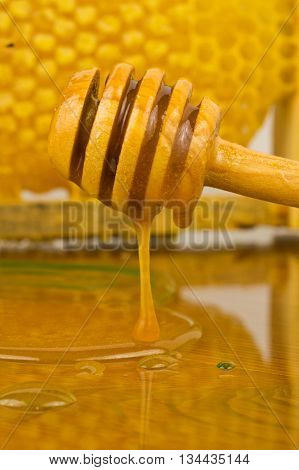 jar of honey with wooden drizzler on honeycomb background