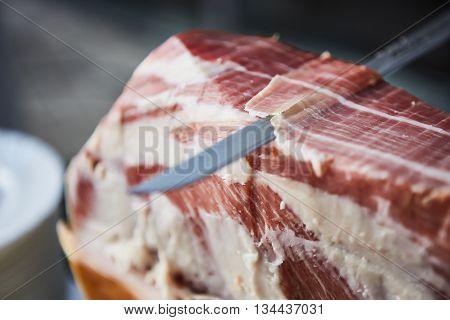 Chef slices serrano ham. Jamon Serrano. Typical Spanish delicatessen. Shallow dof
