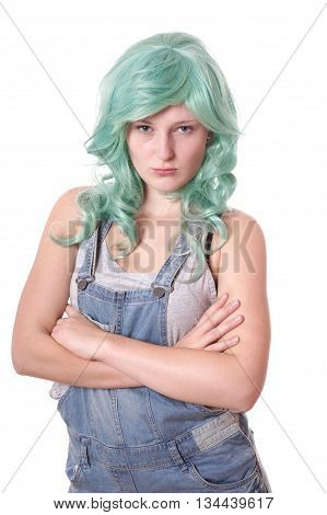 sulking young woman with green hair and jeans dungarees