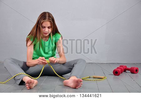 Young muscular teenage girl sitting on the floor with skipping rope and dumbbells relaxing having rest in studio.