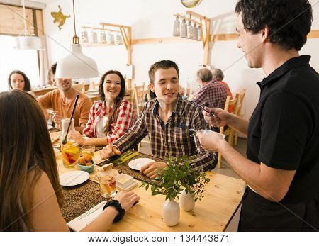 Group of friends at the restaurant and being served by the waiter