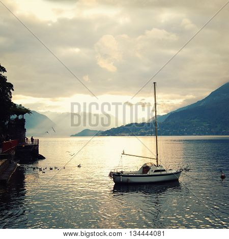 View of Lago di Como at the sunset. Aged photo. Silver linings in Lake Como at the sunset. Aged photo. Sunset view of the lake in Lombardy. Varenna Lake Como Italy.