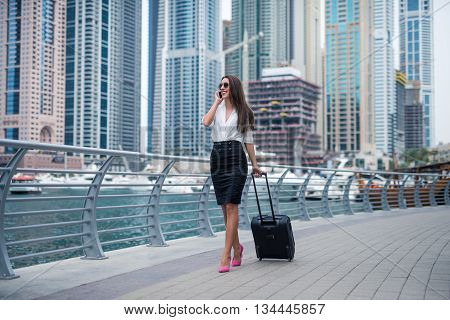 Elegant woman talking on a mobile phone and carrying a luggage.