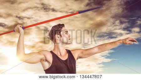 Male athlete preparing to throw javelin against cloudy sky over countryside