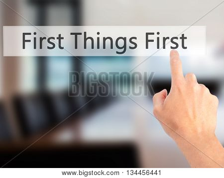 First Things First - Hand Pressing A Button On Blurred Background Concept On Visual Screen.