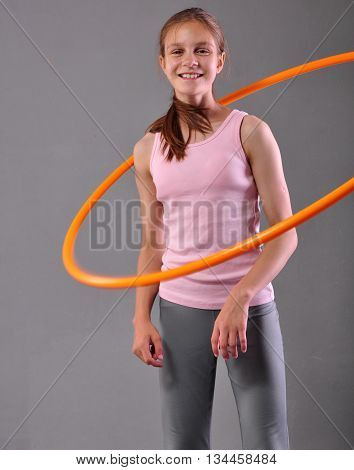 Happy smiling teenage sportive girl is doing exercises with hula-hoop to develop muscle on grey background. Having fun playing game hula-hoop. Sport healthy lifestyle concept.