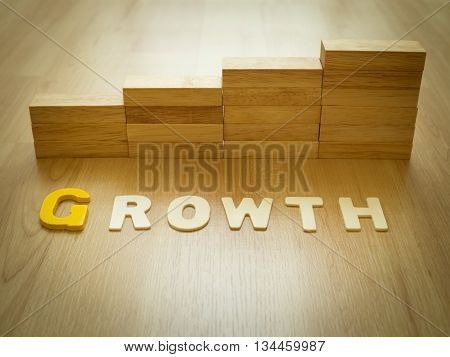 Growth word on wooden floor with wood block stacking as step stair in background. Business concept for growth success process. Growth in career path concept. Vintage filter and selective focus.