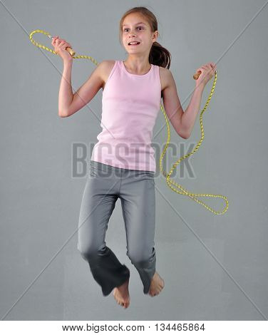 Healthy young muscular teenage girl skipping rope in studio. Child exercising with jumping on grey background. Sporty active childhood concept.