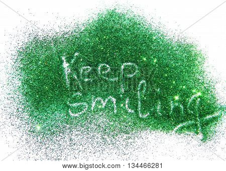 Inscription Keep Smiling on green glitter sparkle on white background