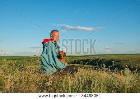 Happy hiker man sitting with a dog in the prairie looking into the distance and smiling. Sunset in a prairie desert. Azov steppes Ukraine.