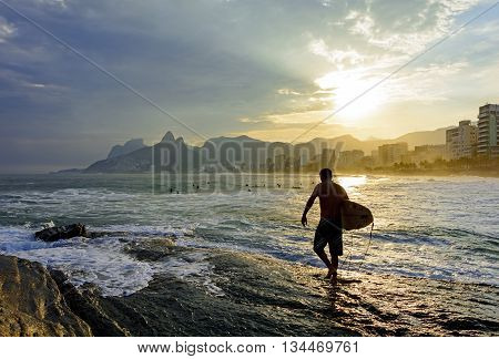 Surfer during sunset in stone Arpoador Rio de Janeiro is preparing to enter the water