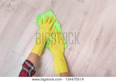 Female hands in yellow gloves wipe the floor rag. poster