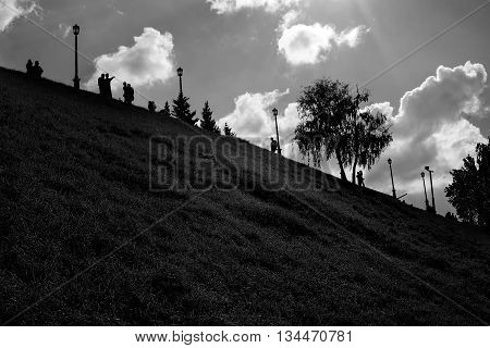 Low key summer black and white park landscape with distant people silhouettes