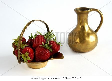 Antique bronze basket of strawberries and jag on white background - shallow depth of field