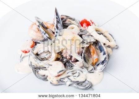 Black pasta with seafood and parmesan in cream sauce. Macro. Photo can be used as a whole background.