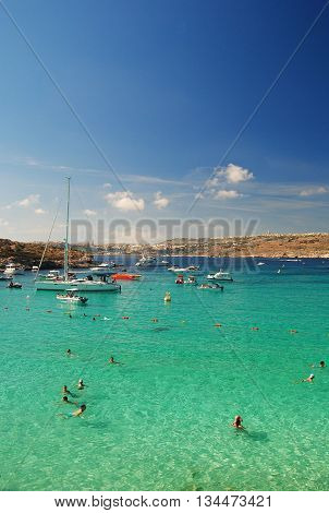 Comino, Malta - September 28, 2013. View of the Blue Lagoon in Comino island of Malta, with people, yachts and Gozo island in the background.