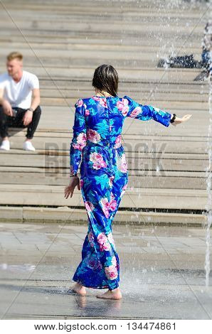 MOSCOW, RUSSIA - May 26, 2016: Unknown girl bathing in city fountain. Hot summer heat. Girls in long wet blue dress. Woman's back. Icy freshness, happiness.