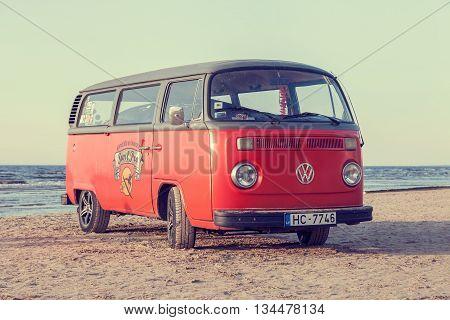 Jurmala Latvia - May 28 2016: vintage red volkswagen bus on beach near the Baltic Sea. Jurmala Latvia. Retro styled photo.
