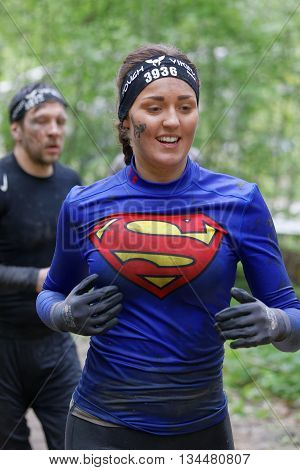 STOCKHOLM SWEDEN - MAY 14 2016: Smiling woman dressed as Superman running in the forest in the obstacle race Tough Viking Event in Sweden May 14 2016