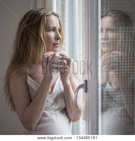 Beautiful blonde drinking morning coffee by the window