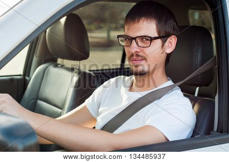 Male caucasian good driver is smiling in his car