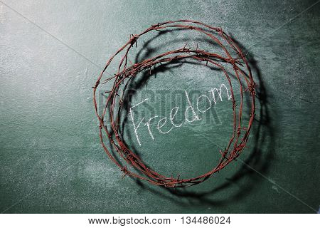 barbwire on top of blackboard with text freedom