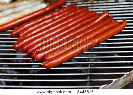Sausage party. Barbecue large grill outdoors. Cookout bbq food. Big roasted pork and beef german sausages, white polish kielbasa. Meat grilled snack. Street food, fast food. Tasty appetizer, sausages.