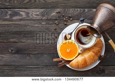 Continental breakfast - cezve and cup of hot coffee croissant and orange. Tasty food on rustic wooden background. Top view place for text.