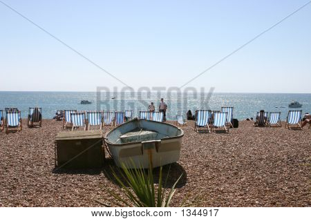 Bright sunny beach setting with a boat and deckchairs