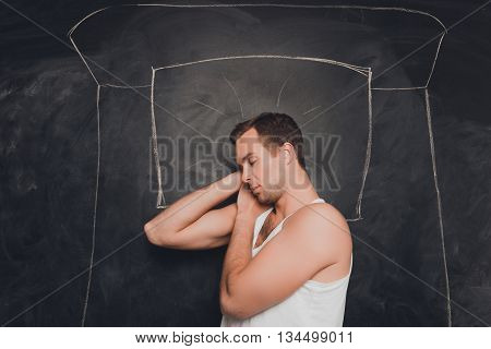 Young  Man Sleeping  On Drawn Bed On The Background Of Blackboard