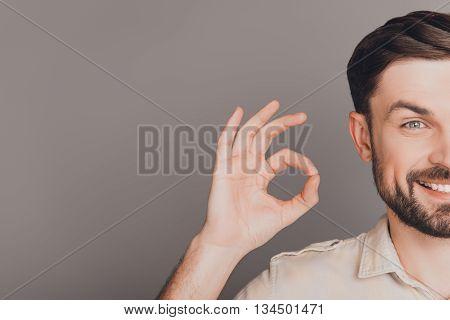 Half-face Portrait Of Cheerful Man Showing Ok Gesture