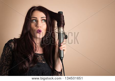 Beauty portrait of woman curling her hair, plenty of copy space