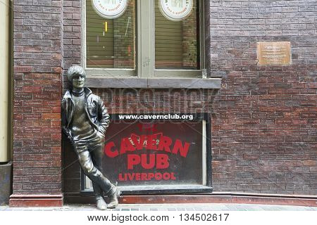 LIVERPOOL, UK. JUNE 09, 2016: Statue of John Lennon at entrance to The Cavern Club, on Mathew Street, where The Beatles played their first concert.