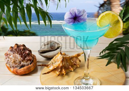 Blue Hawaiian cocktail on the tropical sea background. Iced blue cosmopolitan cocktail. Blue Lagoon cocktail. Blue margarita. Blue curacao liqueur. Iced blue cosmopolitan. Blue moon Cosmo martini
