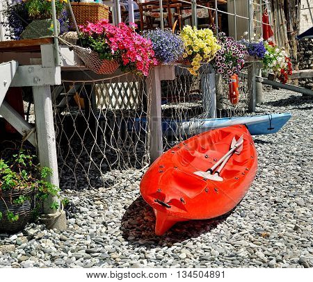 red kayak on sea beach with flowers, and lifeline