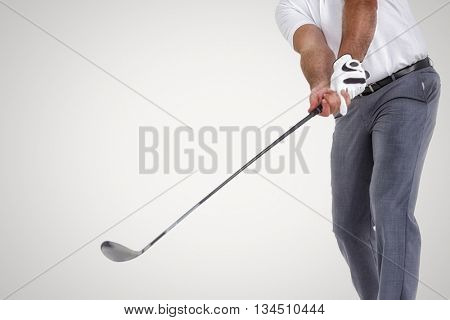 Golf player taking a shot against grey background
