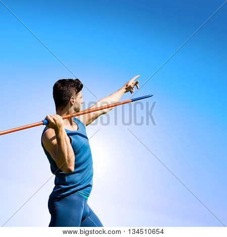 Rear view of sportsman practising javelin throw against blue sky