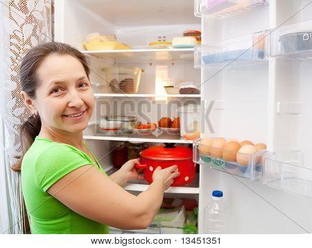 Woman Putting Pan Into Fridge