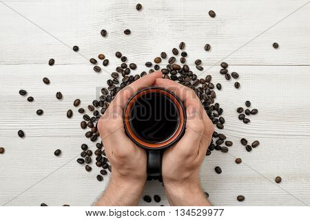 Close-up hands of man holding a cup of coffee. Top view. Workplace of office man. Coffee house. Uplifting mood. Coffee break. Willingness to work overtime. Increasing productivity in the mornings.