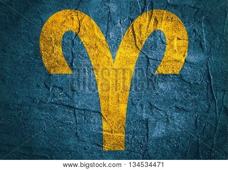 Ram astrology sign. Yellow astrological symbol on concrete textured backdrop