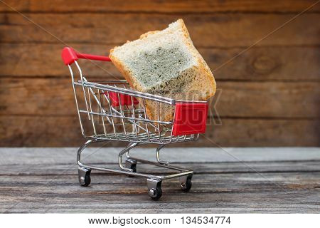 Shopping cart with mold on bread on the old wood background. Mold on food. The concept of selling spoiled food. Toned image.