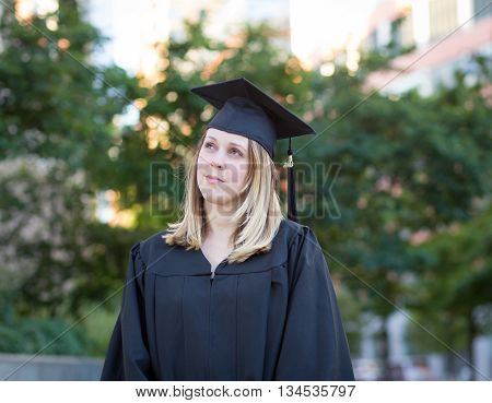 Portrait of female college student on campus in graduation day looking worried and confused