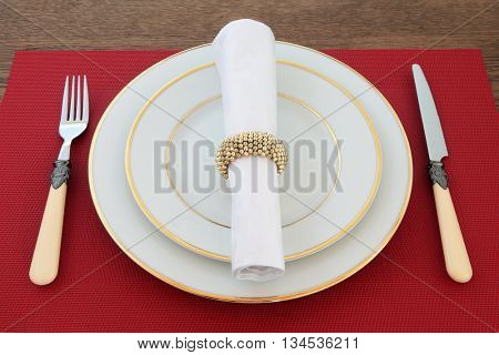 Elegant table setting with white gold rimmed porcelain plates, antique cutlery, linen napkin with ring on red place mat on oak table background.