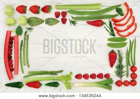 Red and green fresh health food border with vegetable and fruit selection over distressed white wood background. High in vitamins, antioxidants, minerals and anthocyanins.
