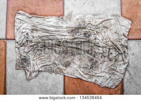 Dirty doormat lies on the pavement slab closeup