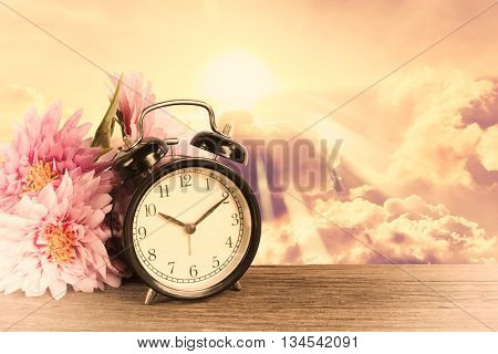 Alarm clock on wood with Golden sky in background. Time of dream Concept.